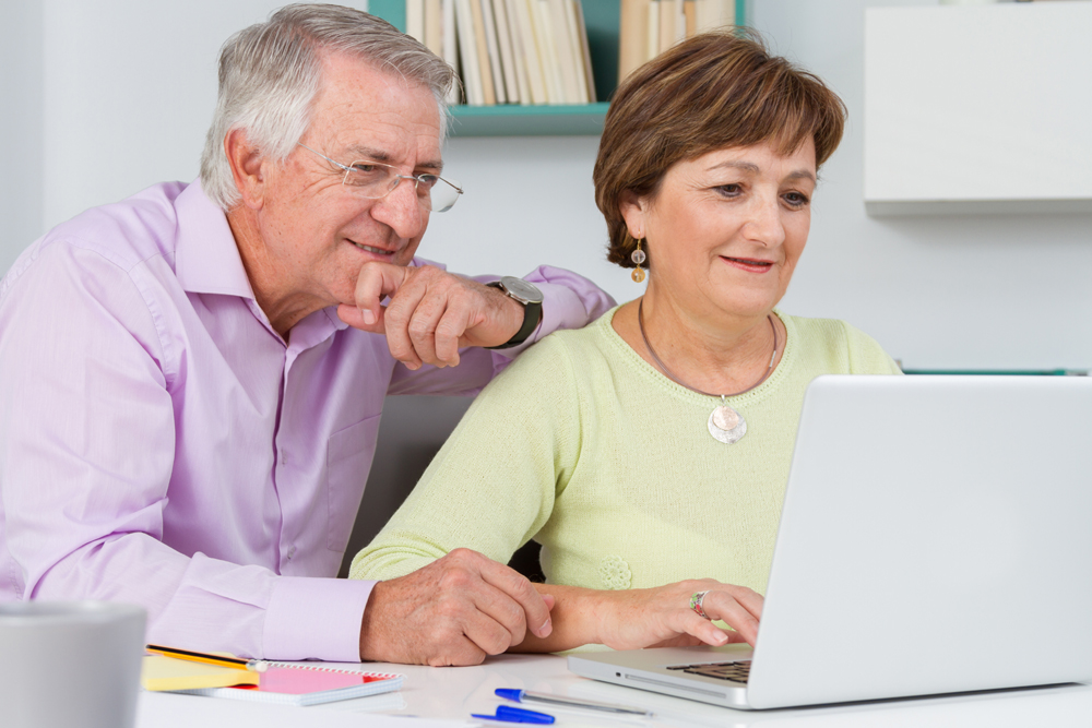 image of a retired couple using at a notebook computer